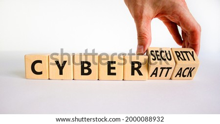Cyber-security vs cyber-attack symbol. Businessman turns wooden cubes, changes words Cyber-attack to cyber-security. Beautiful white background. Cyber-security vs cyber-attack concept. Copy space.