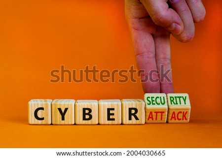 Cyber-security vs cyber-attack symbol. Businessman turns wooden cubes, changes words Cyber-attack to cyber-security. Beautiful orange background. Cyber-security vs cyber-attack concept. Copy space.