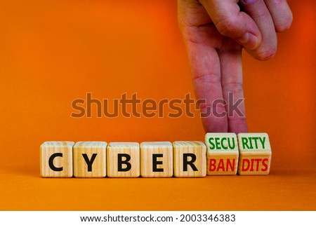 Cyber-security vs cyber-bandits symbol. Businessman turns wooden cubes, changes words Cyber-bandits to cyber-security. Beautiful orange background. Cyber-security vs cyber-bandits concept. Copy space. Photo stock ©