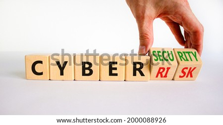 Cyber-security vs cyber-risk symbol. Businessman turns wooden cubes, changes words Cyber-risk to cyber-security. Beautiful white background. Cyber-security vs cyber-risk concept. Copy space.