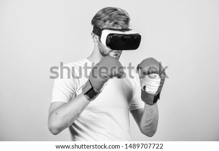 Cyber sportsman boxing gloves. Man play game in VR glasses. Cyber sport concept. Man boxer virtual reality headset simulation. Cyber coach online training. Explore cyber space. Augmented 3D world. #1489707722
