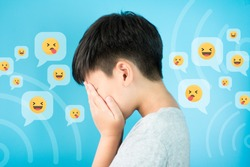 Cyberbullying CONCEPT - A preteen / teen asian boy hands cover his face feeling hurts and stressed from ONLINE 'SOCIAL MEDIA' bullying. Blue background with graphic.