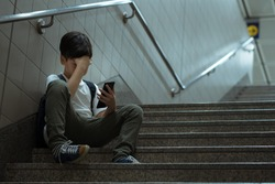 Cyberbullying concept. Young Asian preteen, teenage boy sitting at stair, covering his face with hand, other hand holding smartphone. Alone, stressed, frustrated, overwhelmed, crying, depressed.