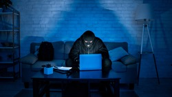 Cybercrime and Spying Concept. Masked criminal using computer at night, making cyberattack, breaking the law