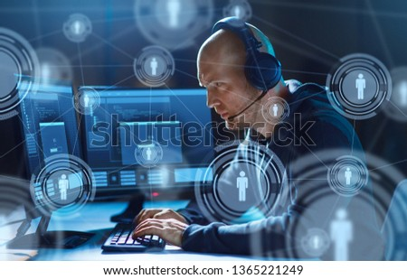 cybercrime, hacking and technology concept - male hacker in headset with progress loading bar on computer screen wiretapping or using virus program for cyber attack in dark room #1365221249