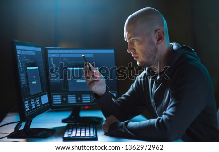 cybercrime, hacking and technology concept - male hacker with smartphone and progress loading bar on computer's screens in dark room #1362972962