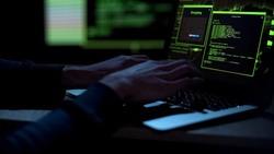 Cybercriminal creating malicious software, typing on laptop keypad, closeup