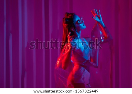 Cyberpunk and neon, a young trend girl in a transparent latex raincoat. Futuristic neon style, bright red backlight. Stylish young woman with glasses and hairdo in Asian anime style