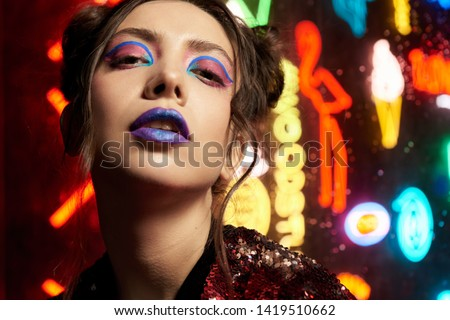 Cyberpunk style close up beauty portrait of girl in futuristic red bathrobe with glitter. She poses against wall of neon figures. Clothes is oversized. Picture has dark noir tones.