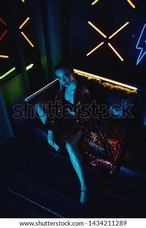 Cyberpunk style portrait of girl in futuristic red glittered bathrobe and tights in net. She poses on leather sofa against neon figures. Set is lit with blue light from TV. Picture has dark noir tone.