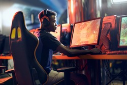 Cybersport concept. Side view of a focused african guy, professional gamer wearing headphones participating in eSport tournament