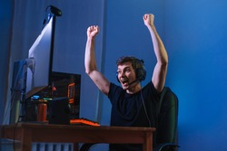 Cybersport gamer feel excited while playing in online cyber sport play, won the game and cheer with hands gesture, screaming, feel glad and happy with his victory. Computer dependence, games obsession