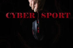 Cybersport. The concept of computer games. A male hand holds a computer mouse on a black background. Modern games