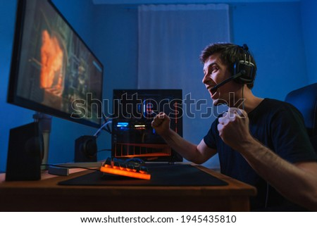 Cybersport young pro gamer happy with winning the game, feel exited, show YES hand gesture, celebrates victory in online game competition. Side view. Guy playing video game at home in his room Photo stock ©