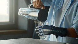 Cyborg guy with artificial limb pours water into glass from large bowl and drinks standing in kitchen against window at home close view