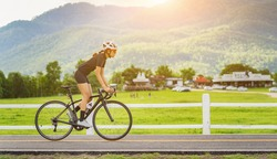 Cycling competition,cyclist athletes riding a race at high speed on mountain road, Sportswomen bikes in the morning,vintage color,selective focus, sports concept,side view,Business competition