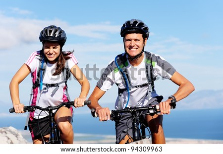 Cycling couple put in extra effort to beat each other to the top of a mountain on their bikes. - stock photo