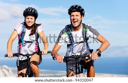 Cycling couple put in extra effort to beat each other to the top of a mountain on their bikes.