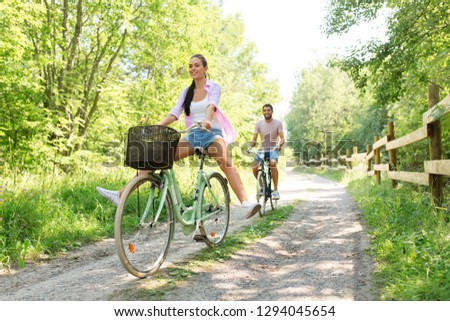 cycling, leisure and lifestyle concept - happy young couple with bicycles at summer park #1294045654