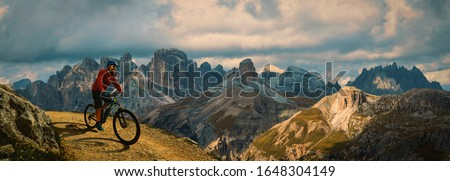 Cycling outdoor adventure. Man cycling on electric bike, rides mountain trail. Man riding on bike in Dolomites mountains landscape. Cycling e-mtb enduro trail track. Outdoor sport activity. Stock foto ©