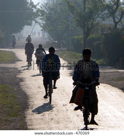 Cycling to work & school in early morning haze. Myanmar (Burma)