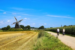 Cycling track with couple of two cyclists in rural flat dutch maas landscape with corn field, trees,   windmill (Molen de grauwe beer) against blue summer sky - Beesel, Netherlands
