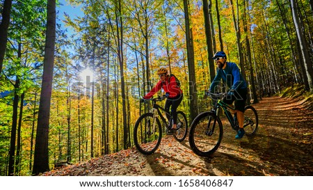 Cycling woman and man riding on bikes at sunset mountains forest landscape. Couple cycling MTB enduro flow trail track. Outdoor sport activity. Photo stock ©