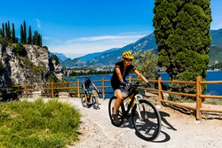 Cycling woman and man riding on bikes in mountains at Garda lake landscape. Couple cycling MTB enduro flow sentiero ponale trail track. Outdoor sport activity.