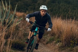 Cyclist boy going down the track on an enduro mountain bike in Barcelona. Man on mountain bike rides on the trail.
