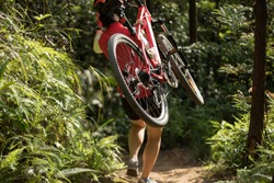 Cyclist carry a mountain bike in the forest