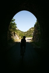 Cyclist coming out of tunnel in the summer forest cave