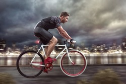 Cyclist cycling in front of a nightly skyline