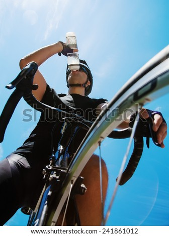 Cyclist drinking water over blue sky