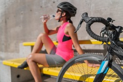 Cyclist drinking water sports bottle, taking a break from cycling bike, touring travel in city during summer vacation. Tired athlete woman with drink, wearing helmet, jersey and shoes.