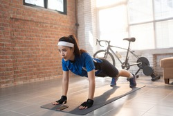 Cyclist exercise with push-ups. She's at home.