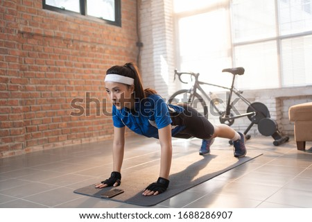 Cyclist exercise with push-ups. She's at home. Foto stock ©