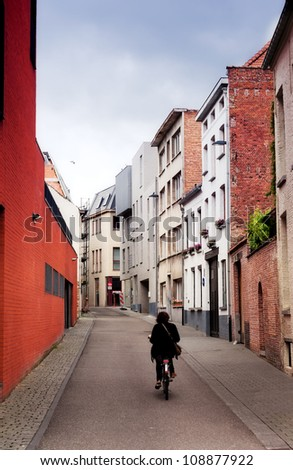 cyclist goes on the ancient narrow street in the Belgian city of Malines (Mechelen)