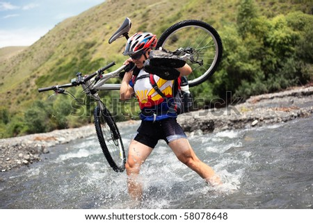 Cyclist goes over the mountain river ford