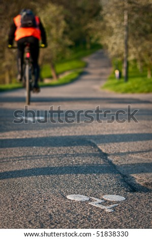Cyclist in a orange vest on a cycleway