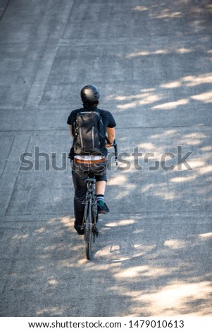 Cyclist in black clothes with a backpack rides a bicycle on a footpath. The use of a bicycle as the main transport for many enthusiasts has grown from a hobby into vital necessity