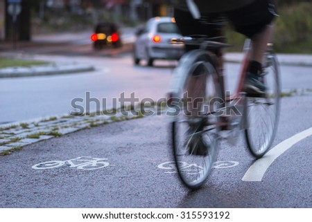 Cyclist in blurred motion on cycling path by busy street at night #315593192