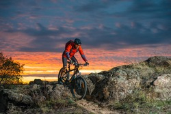 Cyclist in Red Riding the Bike on the Autumn Rocky Trail at Sunset. Extreme Sport and Enduro Biking Concept.