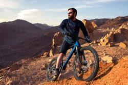 Cyclist in shorts and jersey on a modern carbon hardtail bike with an air suspension fork rides off-road on the orange-red hills at sunset evening in summer
