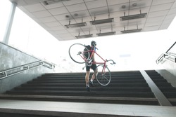 Cyclist in sports wear out of the metro with a bicycle in his hands. Man comes out of an underground passage with a bicycle. Traveling around the city with a bike.Sport concept.