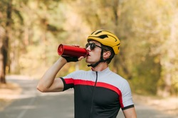 Cyclist in sunglasses, helmet and bike jersey drinks water at workout on a sunny autumn day. Portrait of thirsty man drinking water after cycling. Cycling is a hobby.