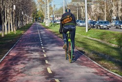 Cyclist in the city is moving along a bicycle path. Eco-friendly mode of transport. View from the back. Bicycle with fixed speed