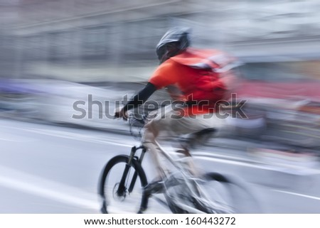 cyclist in traffic on the city roadway motion blur