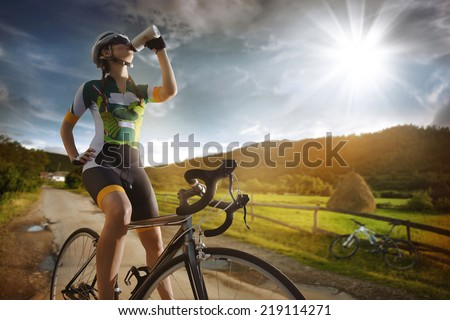 cyclist is drinking water from...