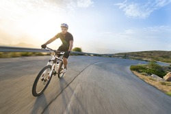 Cyclist man riding mountain bike in sunny day on a mountain road. Image with flare.