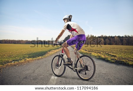 Cyclist on a long road of countryside